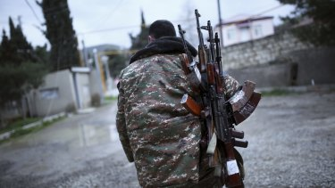An ethnic Armenian fighter carries Kalashnikov machine guns to his comrade-in-arms at Martakert province in the separatist region of Nagorno-Karabakh on Monday.