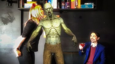 Reload Bar manager Hollie Lehmann and co-owner Jim Andrews kick back with a zombie in Australia's first augmented reality bar.