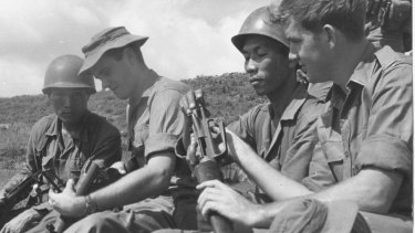 Australian soldiers Private Greg Salmon (left) and Private John Dever show their South Vietnamese allies their weapons in Phouc Tuy province in 1969.