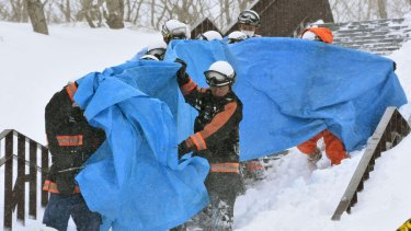 Rescuers carry the people who got injured in an avalanche at a ski resort in Nasu.