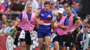 Tom Liberatore is helped off the ground by trainers.