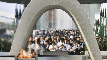People pray for the atomic bomb victims in front of the cenotaph at the Hiroshima Peace Memorial Park on Saturday August 6.