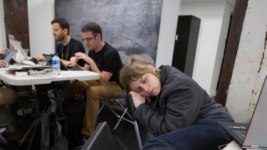 Sarah Erlington sleeps after working on her project all night at the NAB Hackathon in Sydney in November, while Juliius Neggo (left) and Justin Liang chew over ideas.