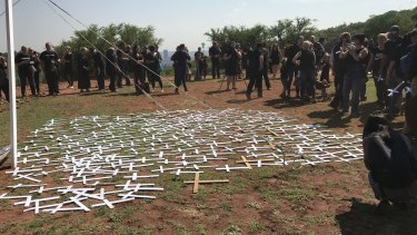 Protesters lay 'cross' symbols on the ground to protest against farmer murders in the country.