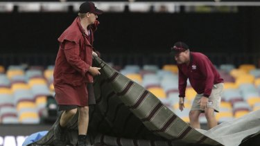 Frustration: Officials cover the pitch after play was suspended due to rain.