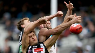Collingwood's Darcy Moore tangles with Port Adelaide's Jackson Trengove.