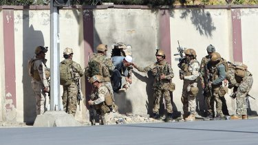 Afghan security personnel rescue a man from the Shamshad TV compound.