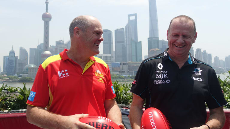 Gold Coast Suns coach Rodney Eade with Port Adelaide coach Ken Hinkley in front of the Pudong skyline in Shanghai.