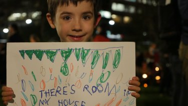 """""""There's room in my house"""" says a sign held by Xavier, who is just two years older than Aylan Kurdi, at the Light the Dark rally in Sydney."""