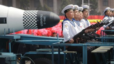 """Navy personnel sit in front of a submarine-launched """"Pukguksong"""" ballistic missile as it is paraded through Pyongyang, North Korea."""