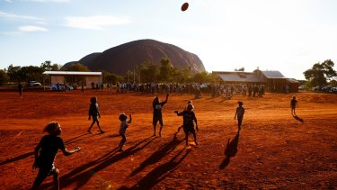 Local children play Aussies rules during the First Nations national convention at Uluru.