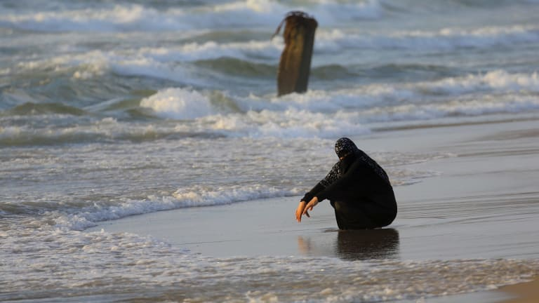 A veiled woman cools off at a beach of the Mediterranean Sea on a sweltering hot day along the coast of Gaza City last week.