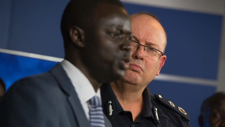 Police Commisioner Graham Ashton listens to African community leader Kot Monoah at a press conference on Wednesday.