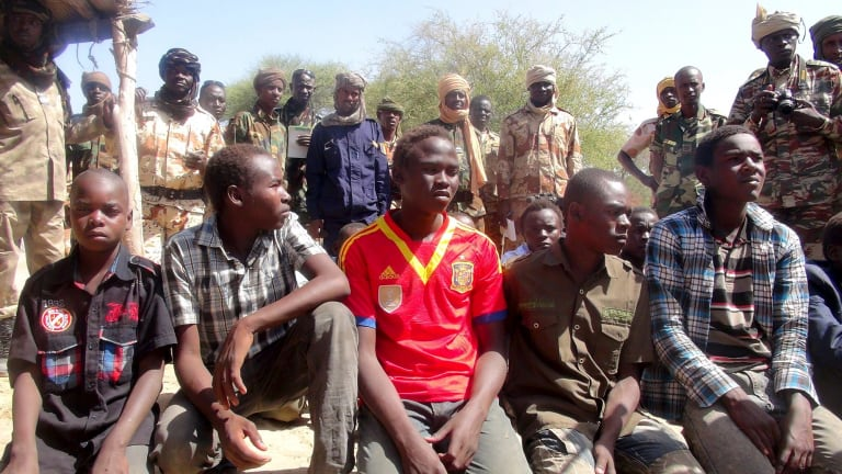 Former members of insurgent group Boko Haram gather in front of Chadian soldiers in Ngouboua, Chad in April.