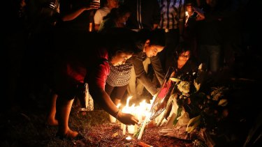 People gather to lay flowers at a memorial site for victim Prabha Arun Kumar.