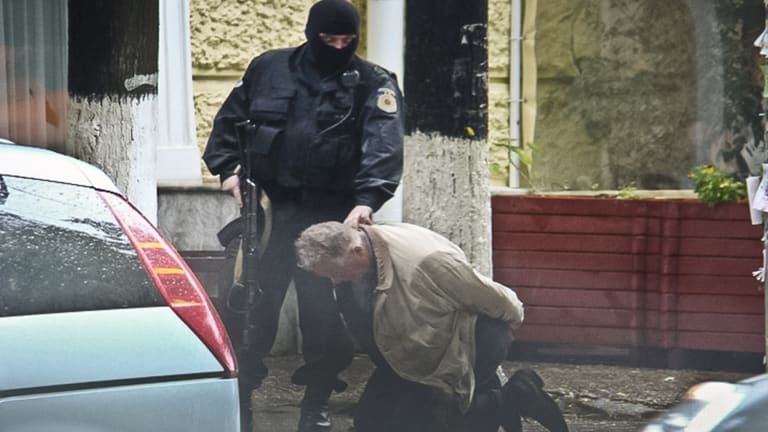Teodor Chetrus is detained by a police officer in Chisinau, Moldova during the uranium-235 sting operation in 2011.