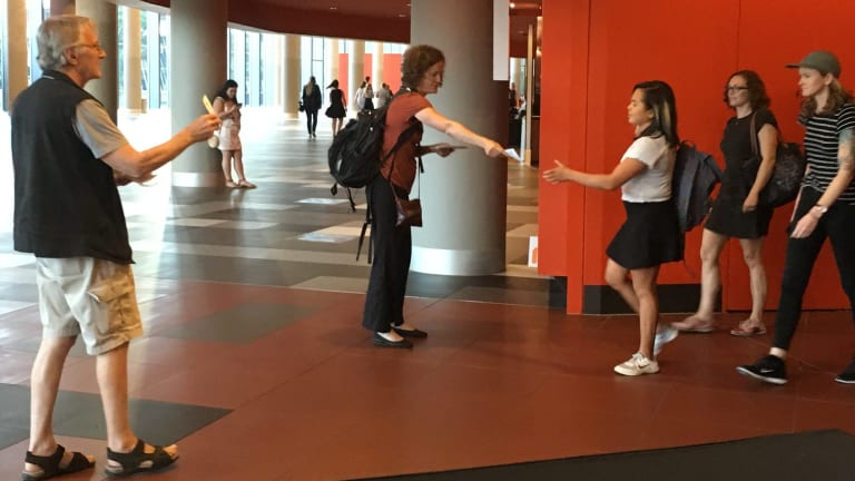 Louise Sales and (left) Bob Phelps of Gene Ethics hand out pamphlets at the Melbourne Convention Centre during the forum.