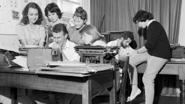 Art students at work preparing the Orientation Week issue of Honi Soit at the University of Sydney. Marie Taylor, Jane Iliff, Madeleine St John and Sue McGowan watch Clive James typing while the editor, David Ferraro, and Helen Goldstein plan other pages, 23 February 1960.
