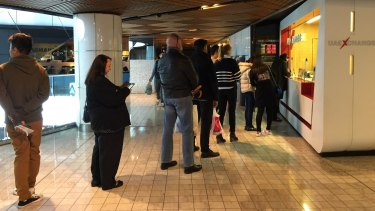 People queue at a currency exchange store in central Sydney to get their hands on pounds.