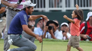 Family matters: Jason Day's son, Dash, congratulates his dad after his dominant display