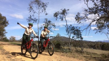 ACT Parks and Conservation volunteer programs manager Alison McLeod and visitor experience manager Jasmine Foxlee riding through Canberra's nature parks on electric mountain bikes.