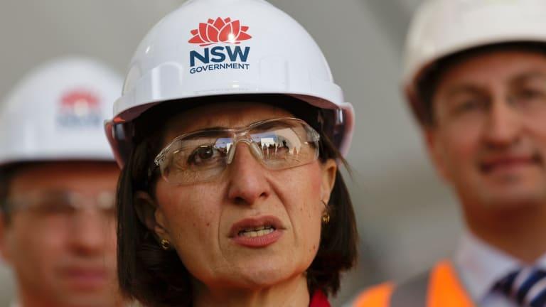 Premier Gladys Berejiklian, in a hard hat bearing the NSW government waratah logo.