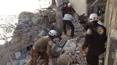 Syrian Civil Defense workers (known as White Helmets) search through the rubble after airstrikes in the village of Hass in the Idlib province, Syria, on Wednesday, October 26, 2016.