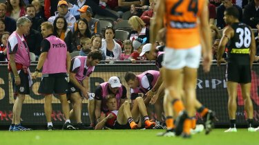 Nick Riewoldt is helped by trainers after the collision.