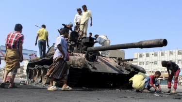 People gather near a tank burnt during clashes on a street in Yemen's southern port city of Aden March 29, 2015.