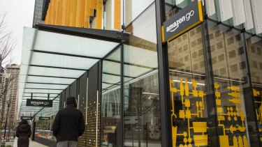 Pedestrians walk past the new Amazon.com grocery store in Seattle, Washington.
