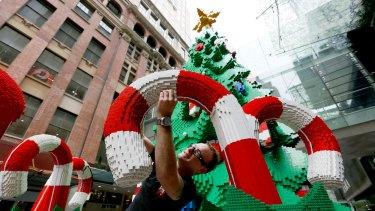 Finishing touches: Johnno Austin puts the final bricks in the Pitt Street Mall Lego Christmas tree.