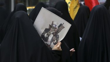 A female Iranian demonstrator with a caricature of Uncle Sam at an anti-US rally in Tehran last month.