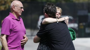 Sandy Phillips, right, whose daughter Jessica Ghawi was killed in the 2012 attack, hugs Eric McQuinn, brother of Matt McQuinn, who was also killed.