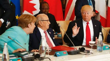 US President Donald Trump talks to German Chancellor Angela Merkel at the G7 summit.