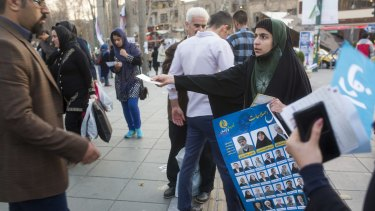A woman distributes election posters in downtown Tehran.
