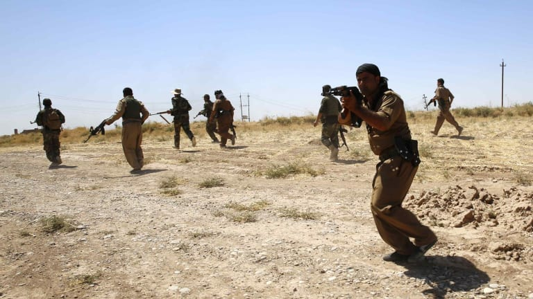 Front line: Kurdish peshmerga fighters advance during clashes with Islamic State on the front line at Buyuk Yeniga village in September.