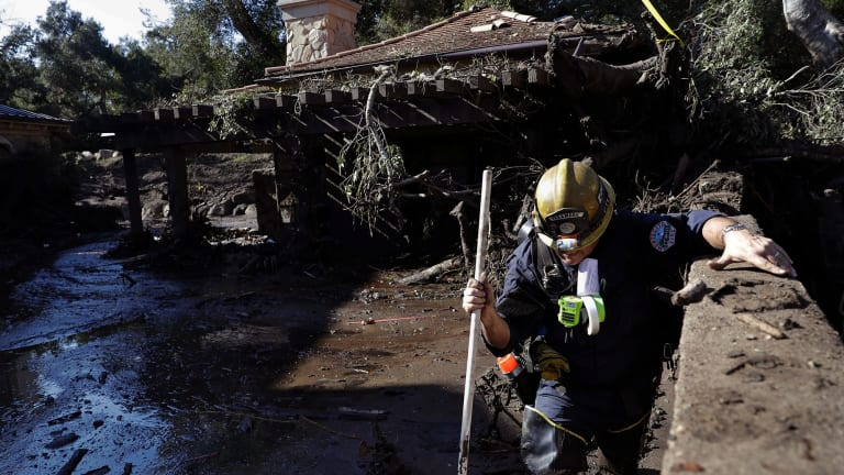 Rescue workers slogged through knee-deep ooze and used long poles to probe for bodies.