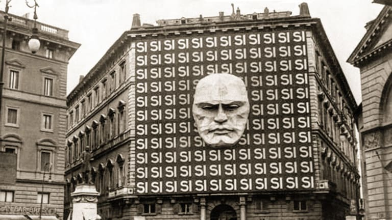 "National Fascist Party headquarters, Rome, 1934, decorated with Benito Mussolini's face and the word Si in reference to the Italian general election which took place in the form of a referendum; voters could either accept or reject the Grand Council of the National Fascist Party, 99.84 per cent of voters voted ""si""."