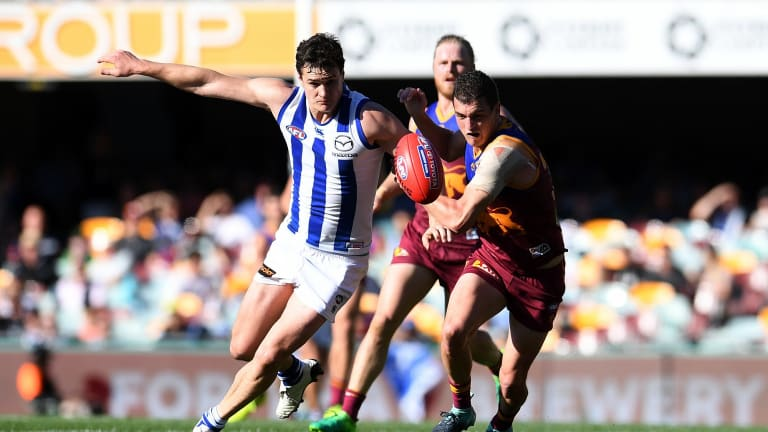 Tom Rockliff of the Lions (right) and Scott Thompson of the Kangaroos chase the ball during the Round 23 AFL game between the Brisbane Lions and the North Melbourne Kangaroos at the Gabba on  Saturday, August 26, 2017.