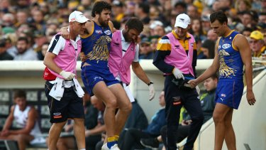 Josh Kennedy is helped from the ground at Domain Stadium with a lower leg injury.