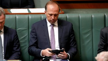 Minister for Immigration and Border Protection Peter Dutton checks his phone. His number was among those leaked.