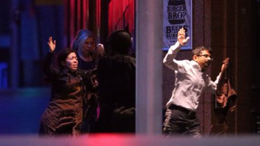 Freed hostages run from the Lindt Chocolat Cafe in Martin Place.