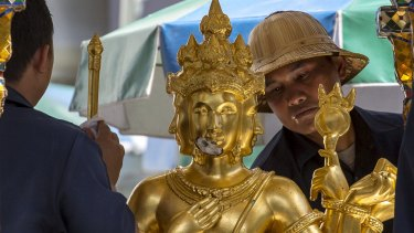 Workers clean a statue of Hindu god Brahma at the Erawan Shrine, the site of the deadly blast.