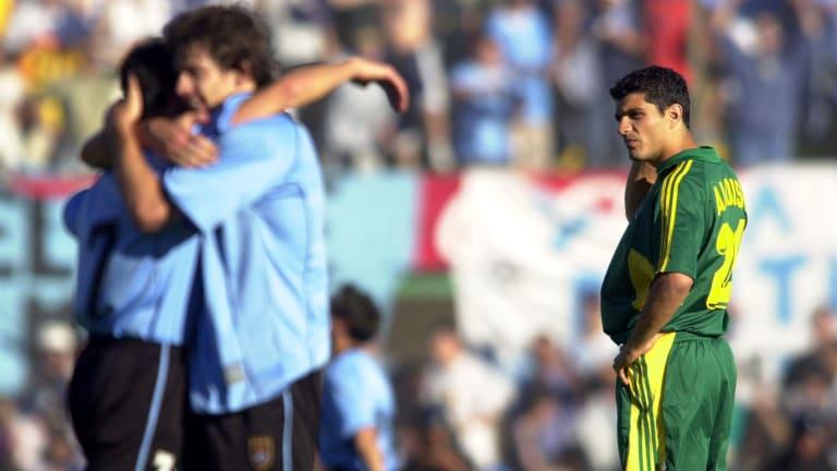 Australia's John Aloisi looks on as Gianni Guigou and Pablo Garcia celebrate Uruguay's win.