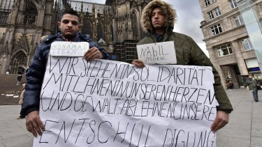 """Mohamad of Lebanon, left, and Nabil of Morocco hold a banner in front of the Cologne cathedral to apologise for other migrants' crimes. The sign reads """"we stand in solidarity in our hearts with you, we refuse  violence and hope you accept our apologize""""."""