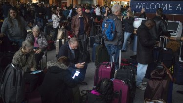 Passengers wait in a dark terminal at Hartsfield-Jackson International Airport during the power outage.