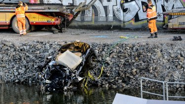 The badly damaged car was retrieved from a canal under the E4 highway bridge in Stockholm on Saturday.