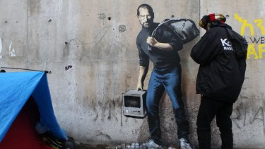 A work by British graffiti artist Banksy at the entrance to the Calais refugee camp in France.
