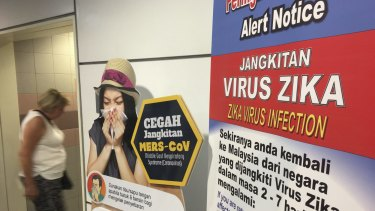 A traveller walks past a travel advisory on the Zika virus infection in Kuala Lumpur International Airport.