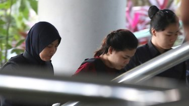 Indonesian Siti Aisyah, centre, is escorted by police as she arrives for a hearing at Shah Alam court house.